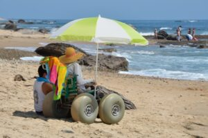 picture of woman on the beach in a beach wheelchair