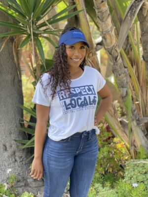 "A woman wearing a ""respect the locals"" t-shirt"