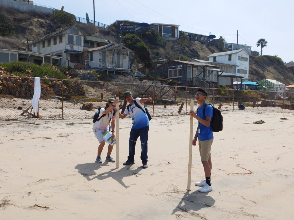 High school students use surveying poles to measure the height of the beach in the Crystal Cove Historic District.